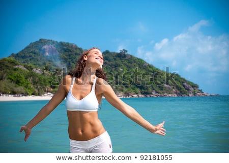 young woman in a bikini splashing in the sea stock photo © smithore