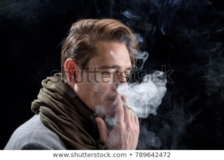 fashion man looking down while enjoying a cigarette stock photo © feedough