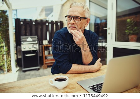 Serious man with laptop sitting at patio Stock photo © wavebreak_media
