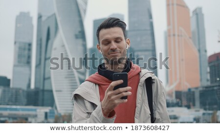 Man with hoodie and mobile phone standing by the window Stock photo © stevanovicigor