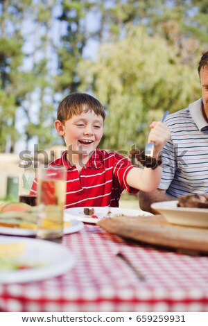 boy serving himself meat at picnic table stock photo © is2