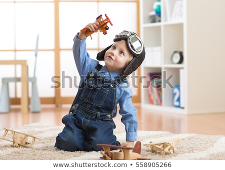 happy little boy playing with airplane toy at home Stock photo © dolgachov