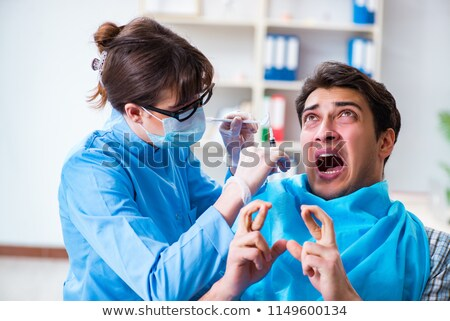 surgeon injecting a scare patient  Stock photo © vladacanon
