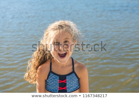 cute little girl stands smiling close to a lake Stock photo © Lopolo