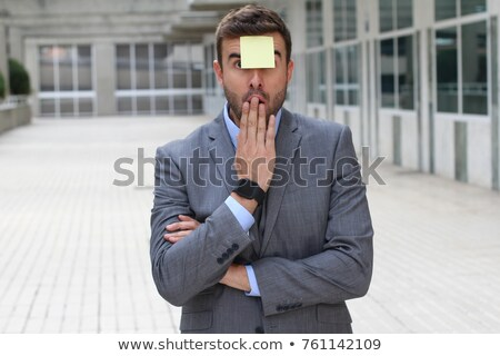 Stock photo: Shocked businessman covered by blank post-it notes.