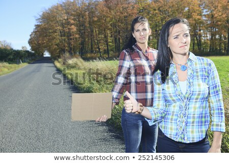 Two Womans asking for a hitch hicking on the road Stock photo © Lopolo