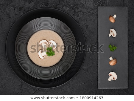 Black restaurant plate of creamy chestnut champignon mushroom soup on black table background with bl Stock photo © DenisMArt