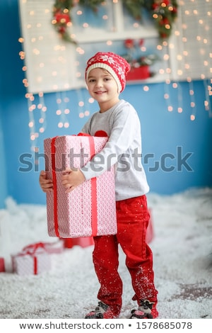 A child surrounded by artificial snow carries a gift in his hands Stock photo © ElenaBatkova
