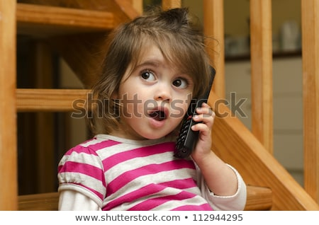 little girl talking mobile phone with surprise stock photo © lunamarina
