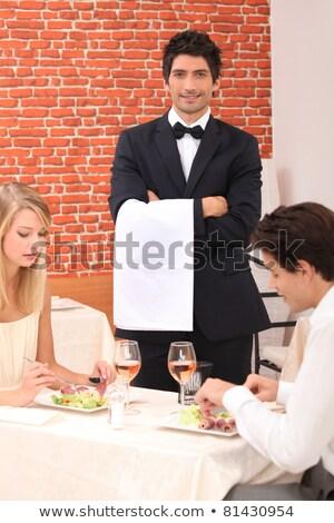 Waiter stood by couple enjoying meal Stock photo © photography33