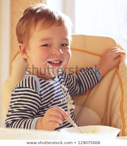Two year old boy eats porridge in the morning. Stock photo © d13