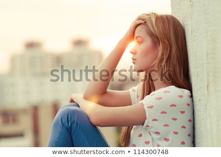 Attractive girl sitting on roof Stock photo © Aikon