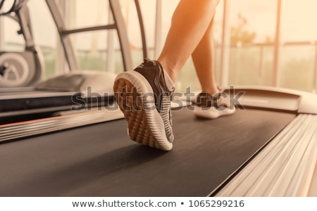Female legs running on treadmill Stock photo © deandrobot