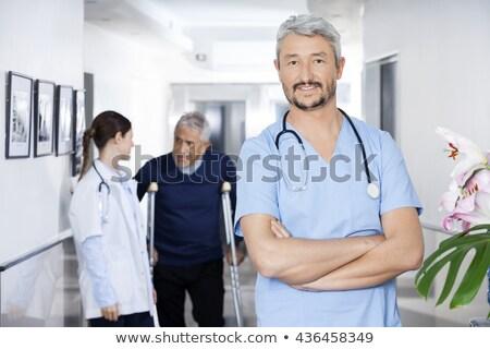 portrait of smiling female doctor with senior man standing by walker against window stock photo © wavebreak_media