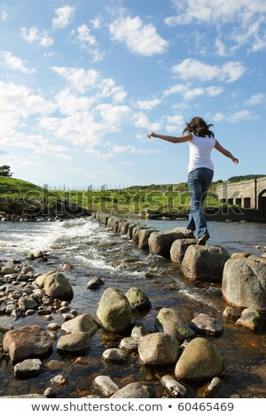 A girl stepping on rocks Stock photo © IS2