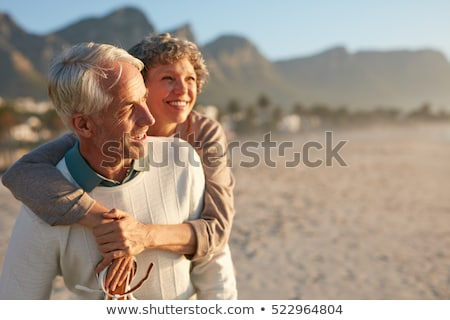 mature couple piggybacking on beach stock photo © is2