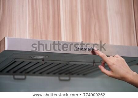 Woman using cooking hood in the kitchen Stock photo © dashapetrenko