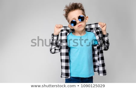 A handsome boy in a plaid shirt, blue shirt and jeans stands on a gray background. The boy supports  Stock photo © Traimak