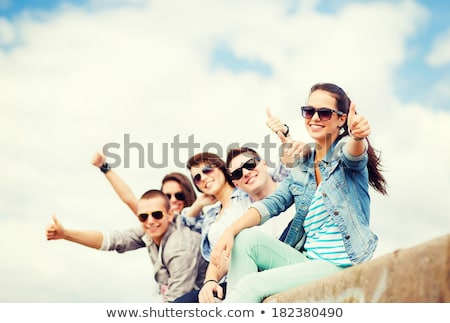teenage girls in sunglasses showing thumbs up stock photo © dolgachov