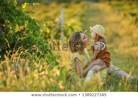 a happy family walking history mother and baby hugging in a meadow yellow flowers on nature in summ stock photo © elenabatkova