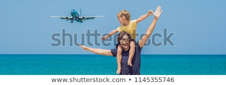 Dad and son have fun on the beach watching the landing planes. Traveling on an airplane with kids co Stock photo © galitskaya