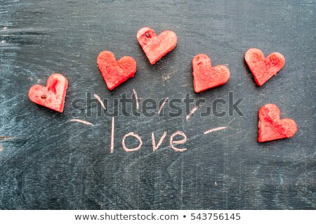 Water melon cut into heart shape. Inscription love with chalk. Flat lay composition. Valentine's Day Stock photo © galitskaya
