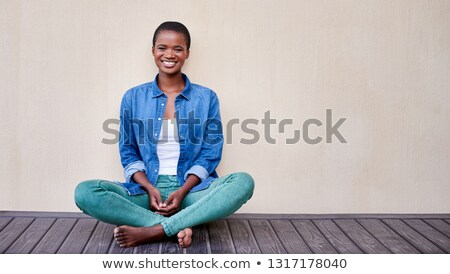 Smiling relaxed African American female sits crossed legs on bench against kitchen interior, wears w Stock photo © vkstudio