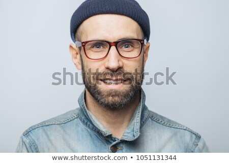 Close up of attractive blue eyed unshaven male witth pleasant appearance has delighted look, wears d Stock photo © vkstudio