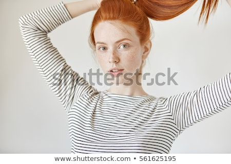 smiling red haired girl holding to her head Stock photo © dolgachov