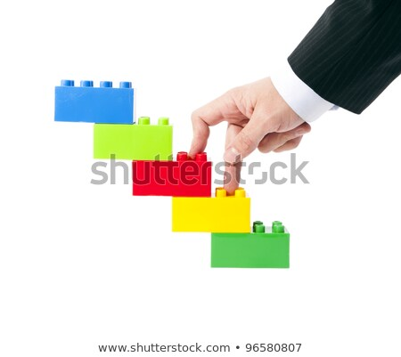 Stock photo: Symbolic construction toys, and a businessman's hand.