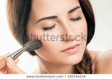 Young woman applying rouge with blusher brush Stock photo © rosipro