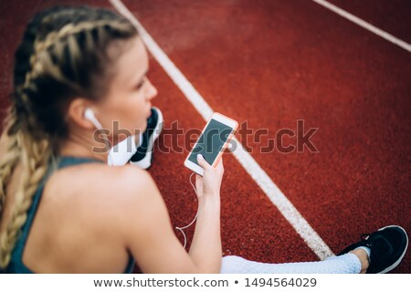 Sportswoman with earphones and blank screen smartphone using treadmill  Stock photo © deandrobot