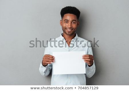 lezser · fiatalember · tart · lap · papír · mosolyog - stock fotó © nyul