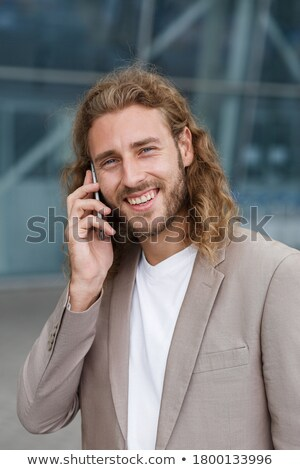 Happy smiling man with curly hair talking on mobile phone Stock photo © deandrobot