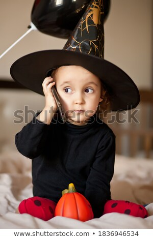 laughing woman in halloween costume holding smartphone stock photo © deandrobot