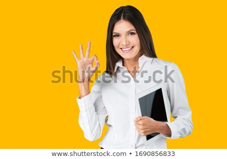 smiling casual woman holding tablet makes ok sign stock photo © feedough