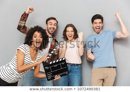 Excited group of friends holding film making clapperboard. Stock photo © deandrobot