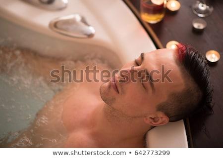 Guapo joven relajante bañera de hidromasaje spa agua Foto stock © boggy
