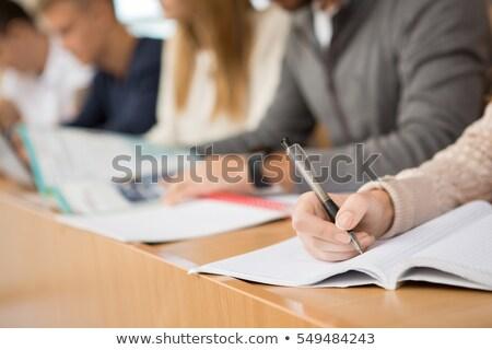 Young student writing during brainstorming for a group assignment Stock photo © Kzenon