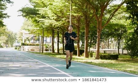 Poważny młodych asian człowiek jogging parku Zdjęcia stock © deandrobot