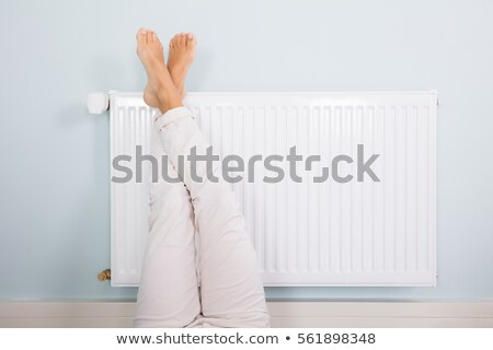 woman warming up her feet on radiator stock photo © andreypopov