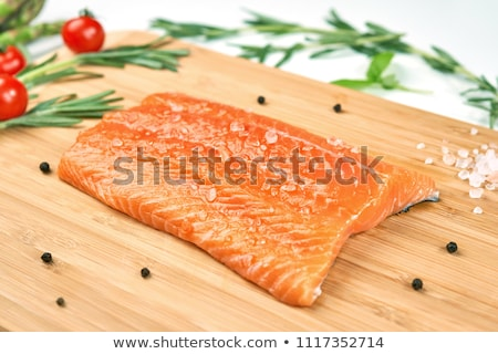 Fresh raw salmon slice on chopping board with pepper tomatoes and lemon on stone kitchen table backg stock photo © DenisMArt