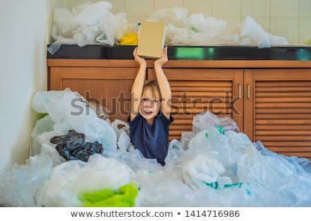 The boy's parents used too many plastic bags that they filled up the entire kitchen. Boy shows them  Stock photo © galitskaya