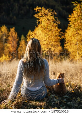 Pretty, young woman with her cat pet sitting in grass  stock photo © lightpoet