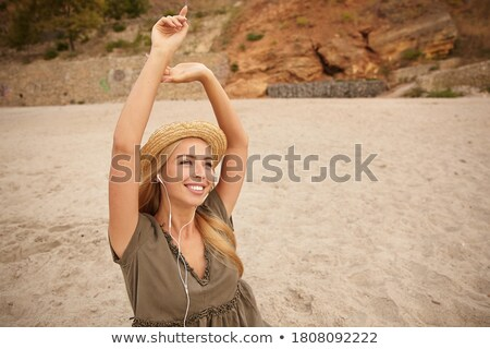 Pleased lovely woman with long hair, keeps hand raised, wears fashionable shirt, has clam face expre Stock photo © vkstudio