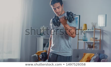 Muscular Man Exercising Biceps With Dumbbells Stock photo © Jasminko