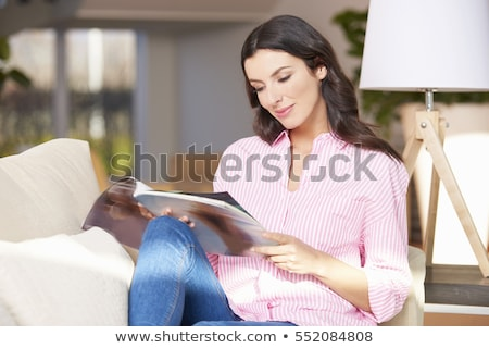 Happy woman lying on lounge reading magazine Stock photo © Giulio_Fornasar