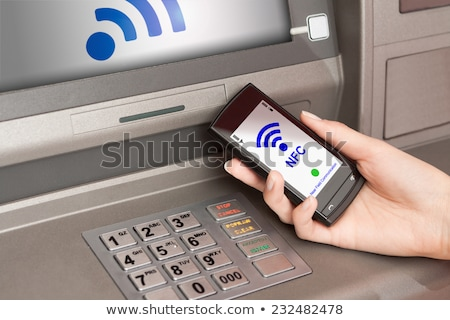 withdrawing money atm with mobile phone a NFC terminal Stock photo © REDPIXEL