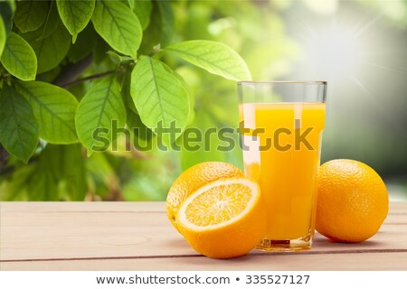 Oranges with a glass of orange juice in the foreground Stock photo © raphotos