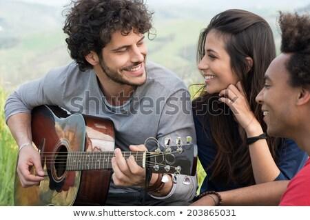woman looking at friend playing guitar stock photo © wavebreak_media